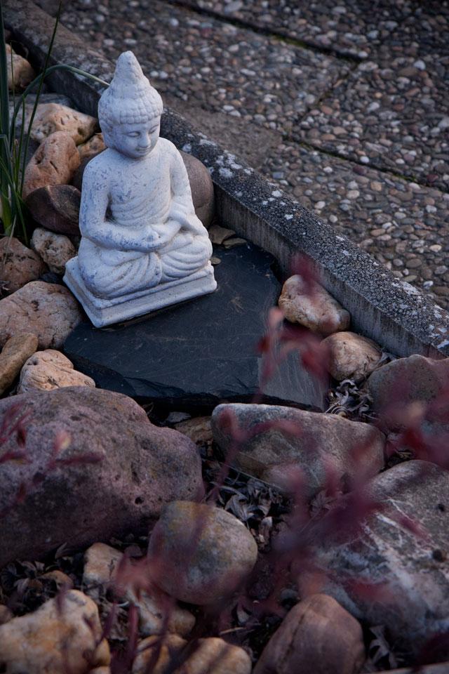 Steingarten mit einer kleinen weis(s)en Gottheit.