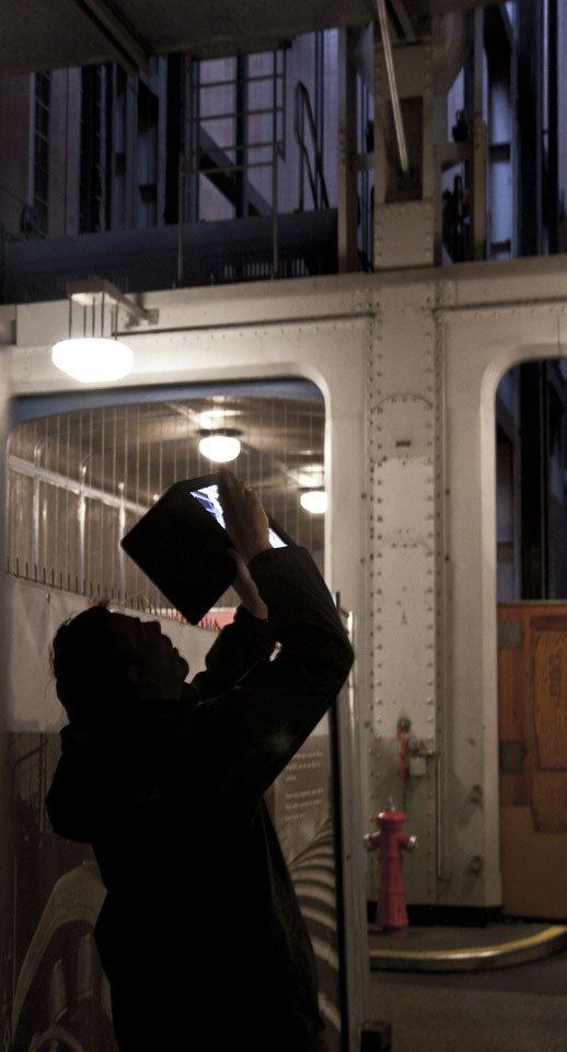 Neue Technik meets alte Technik: mit dem iPad fotografiert dieser Mann die alten Aufzüge für Autos.