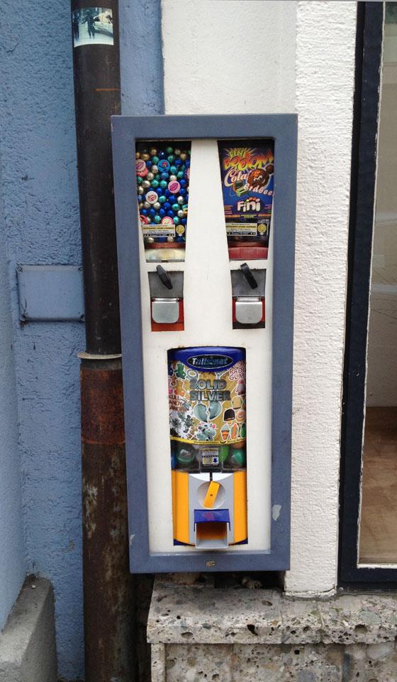 Extra schmal und fast in Tarnfarbe vor der Wand – Automat gesehen in St. Johann im Pongau in der Altstadt