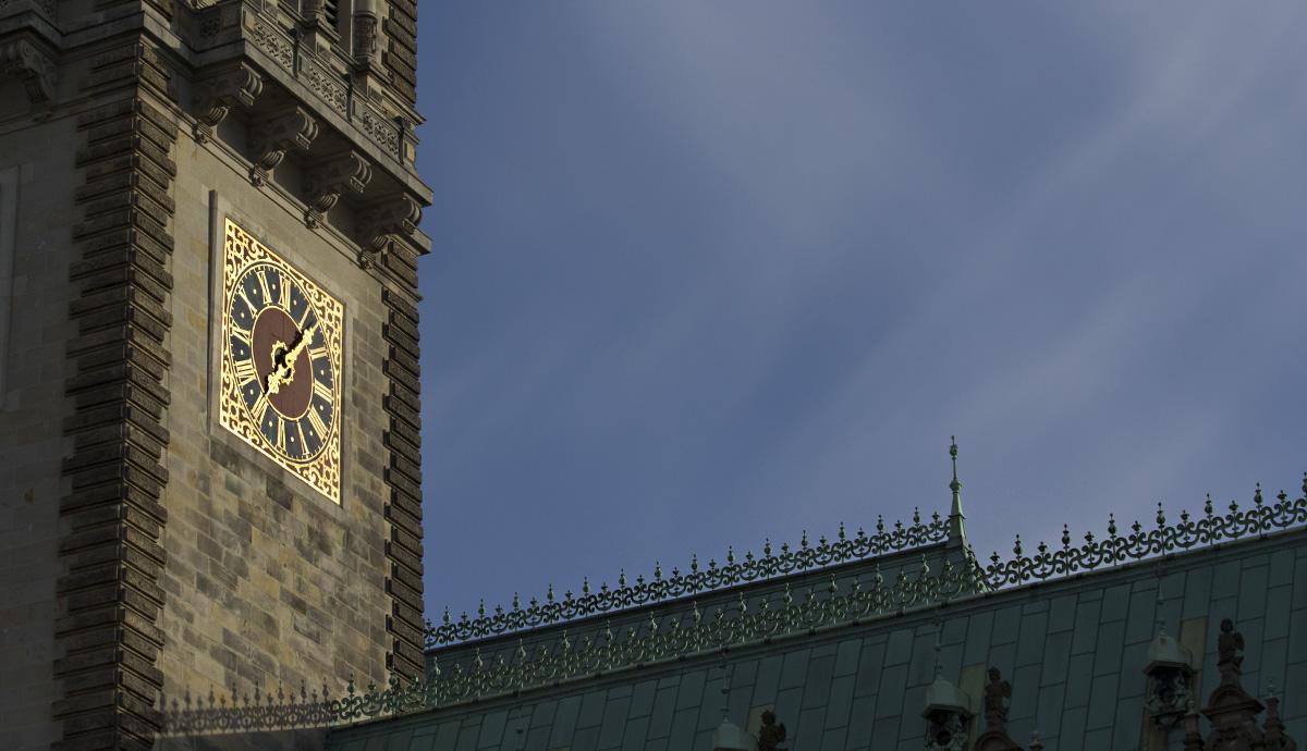 Leuchtet in den letzten Sonnenstrahlen – die Uhr am Turm des Hamburger Rathauses.