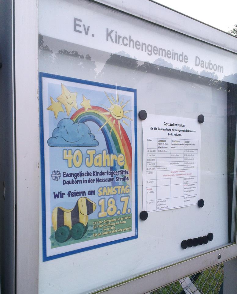 Das Plakat auf dunkelblauem Karton im Schaukasten der Evangelischen Kirchengemeinde Dauborn.