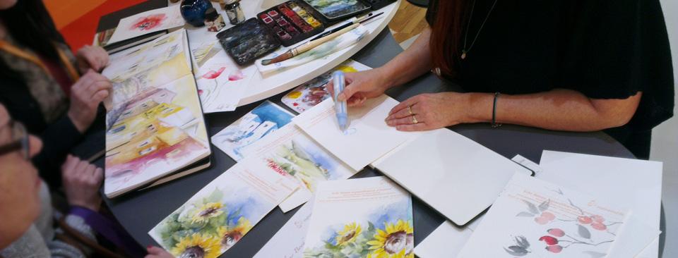 Audry Backs demonstriert die Arbeit mit Rubbelkrepp als Vorbereitung eines Aquarells, während weitere Besucher das neue Hahnemühle Aquarell-Skizzenbuch begutachten.