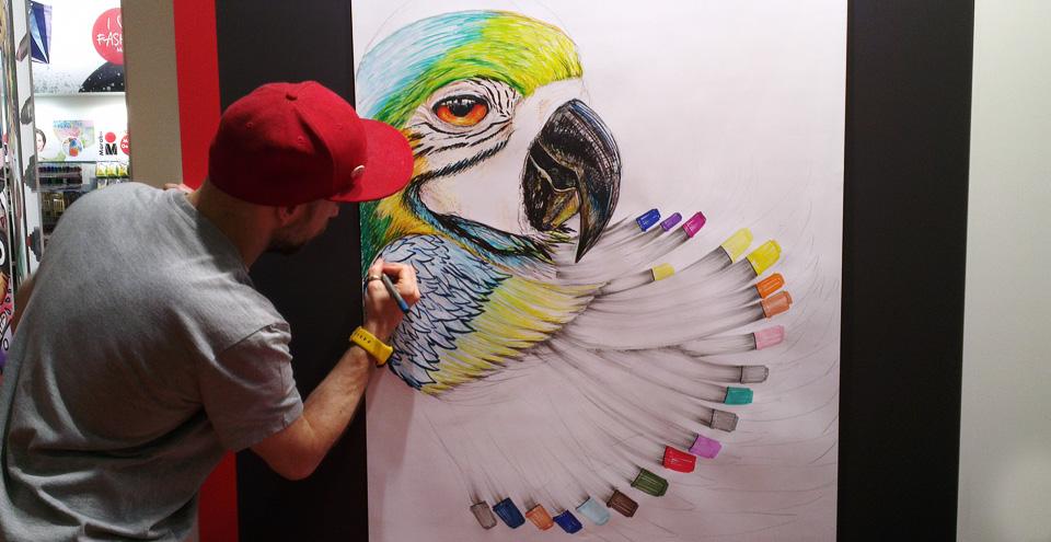 Der Künstler am Marabu-Stand lässt das neue Produkt in seine Illustration einfließen.