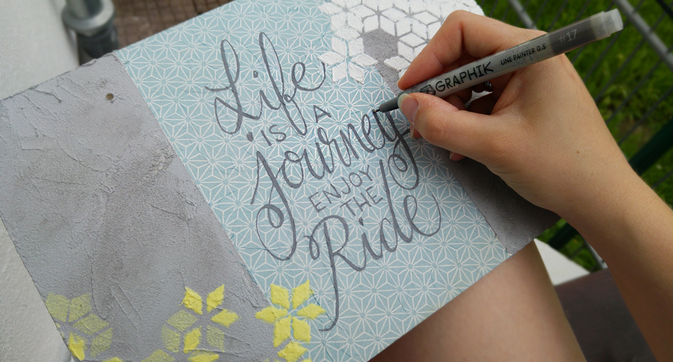 """Life is a journey – Enjoy the Ride!"" mit Derwent Graphik in Grau geschrieben."
