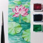 Die Lotusblüte ragt mit ihrer auffälligen Farbe aus dem Wasser heraus.