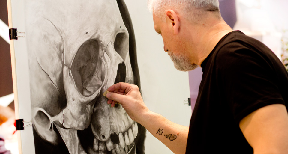 Wilfried Ploderer arbeitet an einem großformatigen Totenkopf während der Messetage am Stand von Cretacolor.