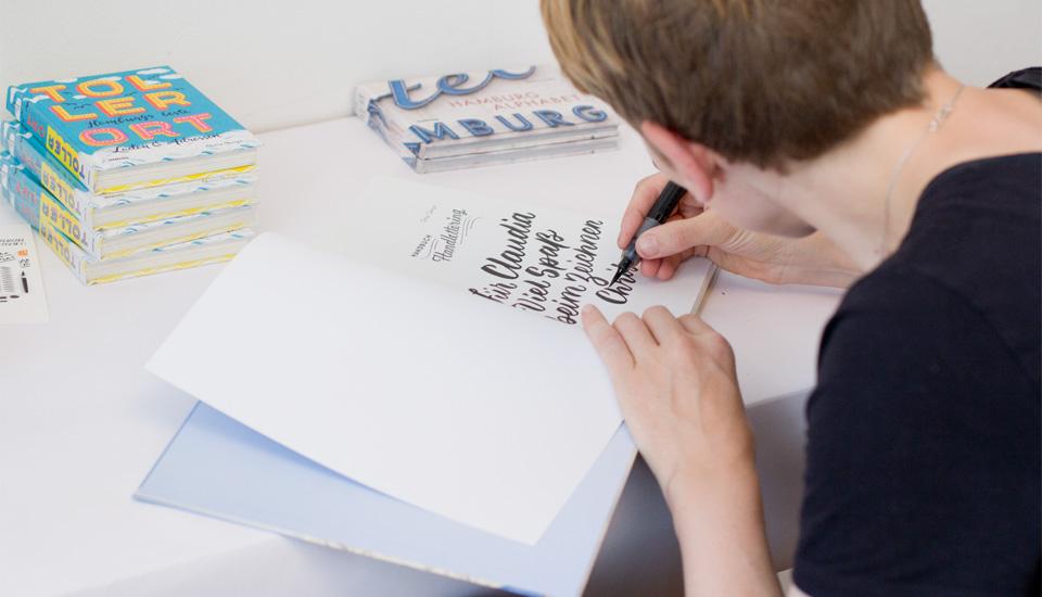 Während die Teilnehmer fleißig üben, signiert Chris Campe Bücher für sie.