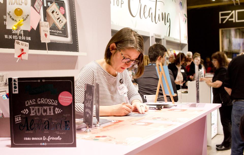Frau Annika schreibt Sprüche mit weißen Markern und erfüllt auch Autogrammwünsche beim Frechverlag.