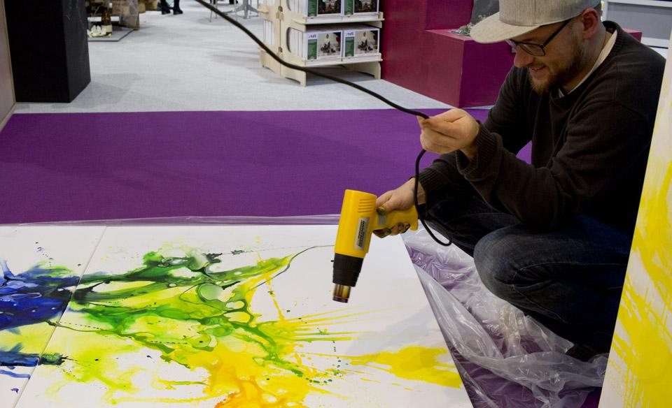 Messejob: Da hier das Bild schneller trocknen soll, muss der Künstler etwas nachhelfen mit dem Heißluftfön.