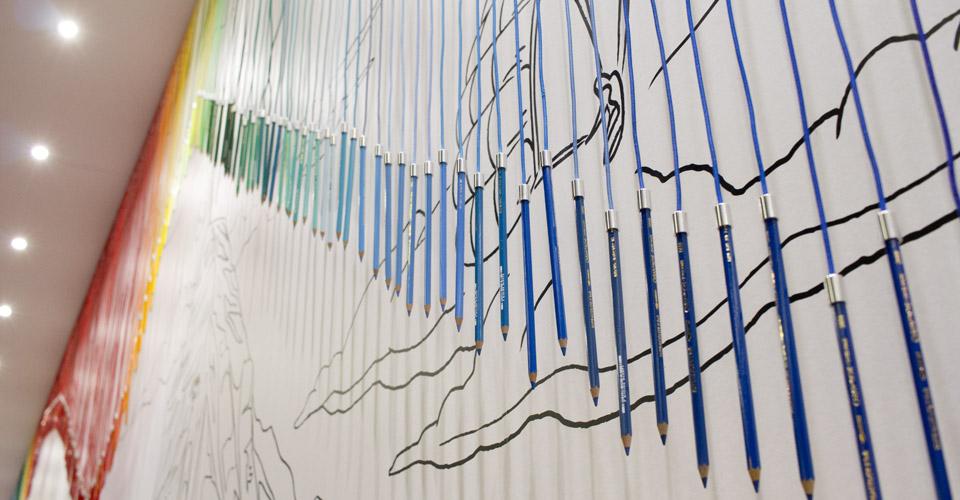 Ein Regenbogen aus Buntstiften von Caran d'Ache hängt von der Decke.
