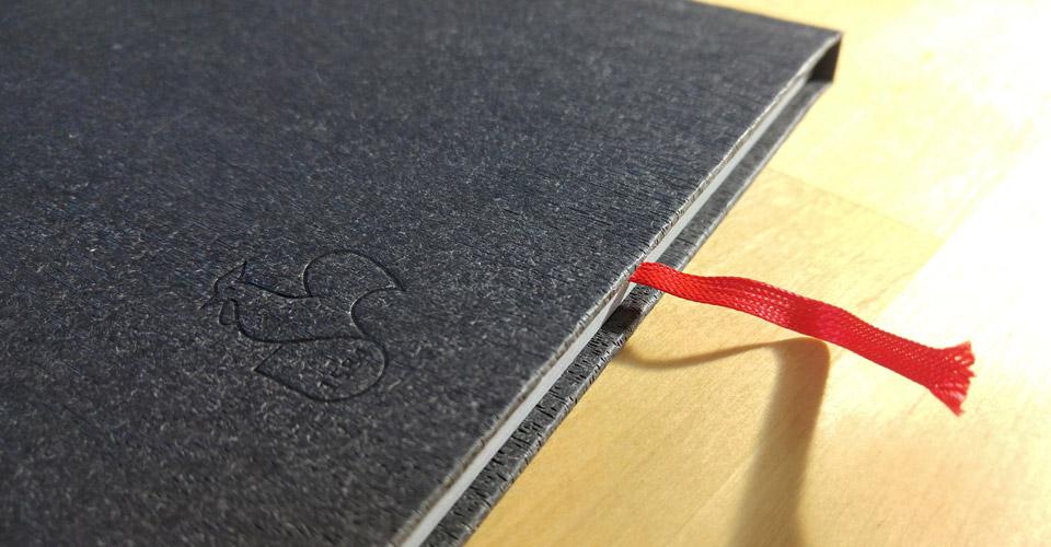 Feiner Umschlag mit Holzmaserung und der Logoprägung auf der Rückseite.
