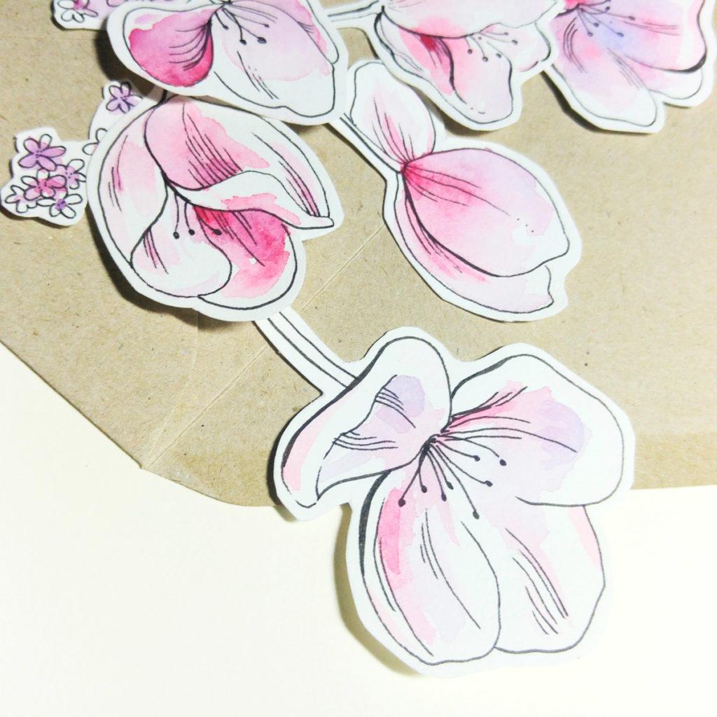 Einzelne Blüten zusammen mit dem Briefumschlag aus Kraftpapier arrangiert.