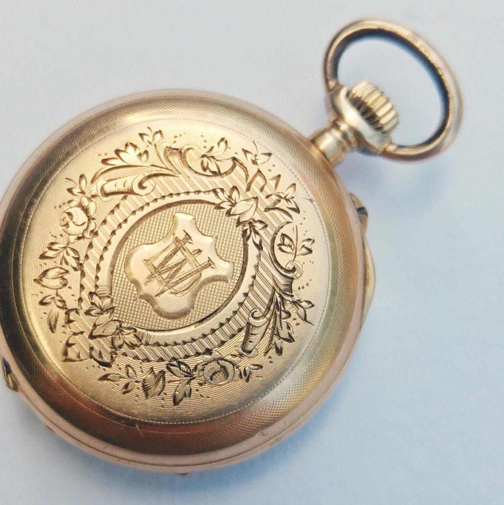 Handwerkskunst – die kleine goldene Taschenuhr und die Gravur auf der Rückseite.