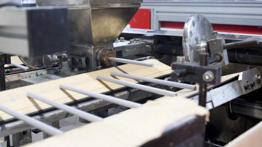 Die Stift spuckende Maschine?! Nein, hier werden die Holzstifte mit dünnem Wasserlack überzogen.