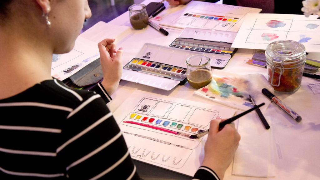 Blick über die Schulter, wie die Teilnehmer ihren eigenen Kasten colorieren.