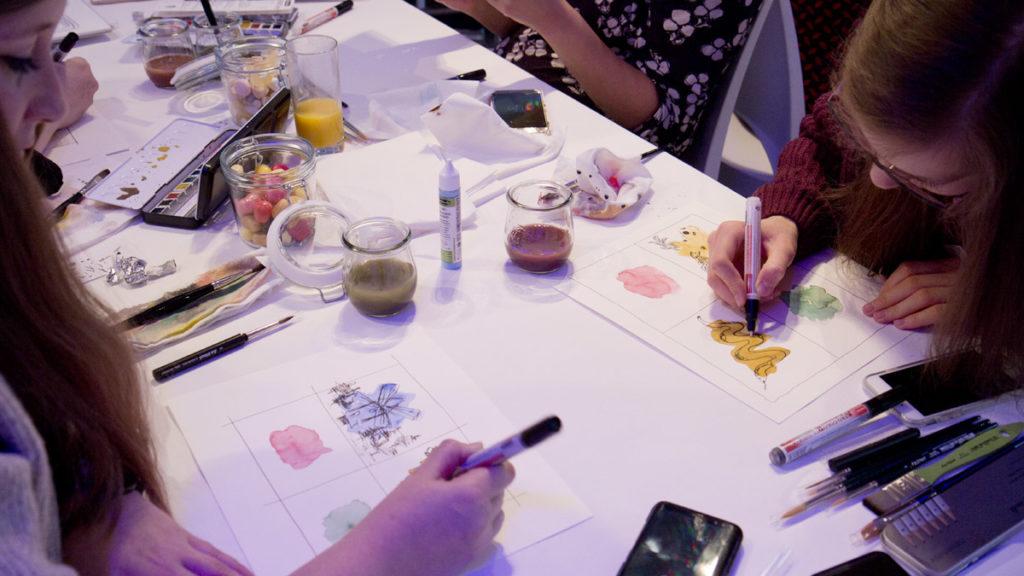 Gemeinsame Übungen am Tisch mit Aquarellflecken und Fineliner.