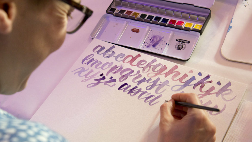 Hier ist Chris in ihre Element: Buchstaben mit dem Pinsel schreiben.