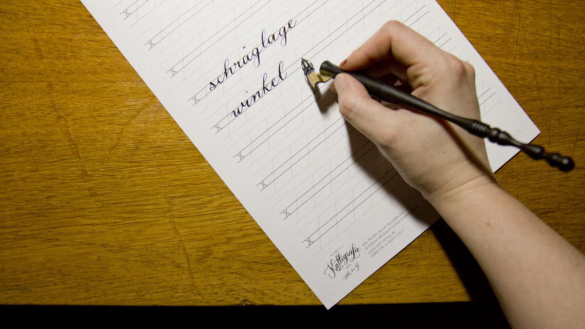 Eingerichteter Arbeitsplatz: Das Papier liegt schräg nach links gekippt, dadurch ist der Winkel leichter zu schreiben, die Schrift bekommt ihre elegante Schräglage.