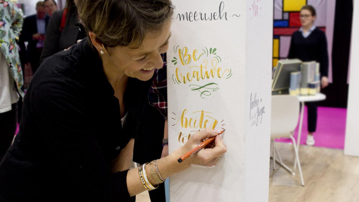 """Diana Soriat lettert ihr """"Heiter weiter"""" an die Säule des Semikolon Standes."""
