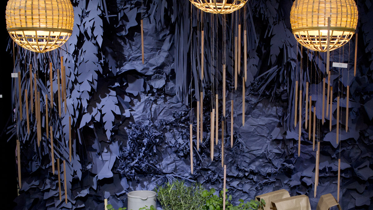 Geflochtene Lampen von denen wie ein Mobile Holzstifte herab hängen.