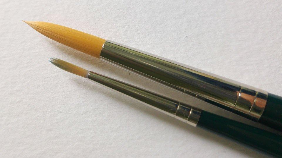 Die dünnere Pinselspitze wurde bereits mit Acrylfarben genutzt, die größere wird noch durch Gummi Arabicum fest in ihrer Form gehalten.