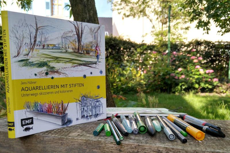 """Das Buch """"Aquarellieren mit Stiften"""" von Jens Hübner mit einer kleinen Auswahl an Stiften aus meinem Sammelsurium, die im Buch Erwähnung finden."""