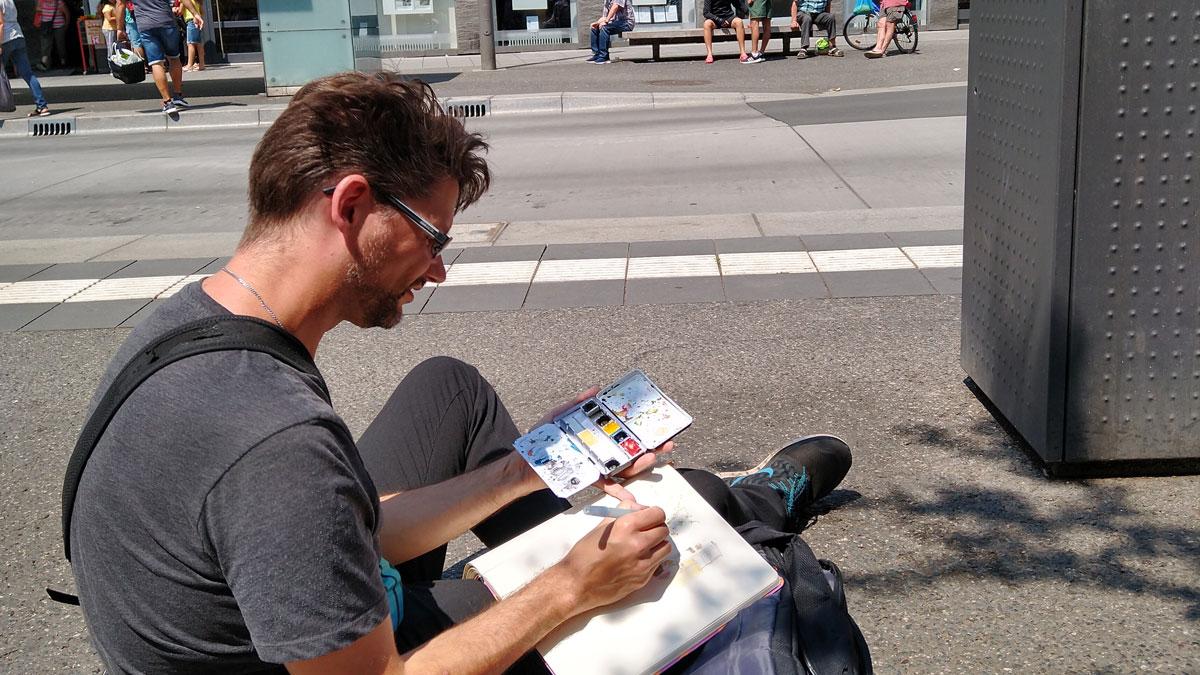 Sahs Eike in der Sonne auf dem Boden der Bushaltestelle und zeichnete die Performance.