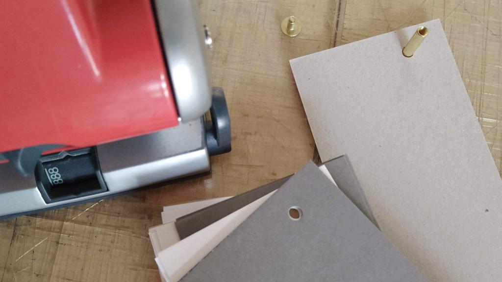 Mit der Rückpappe beginnend werden die gelochten Papiere auf den Schaft der Buchschraube sortiert.