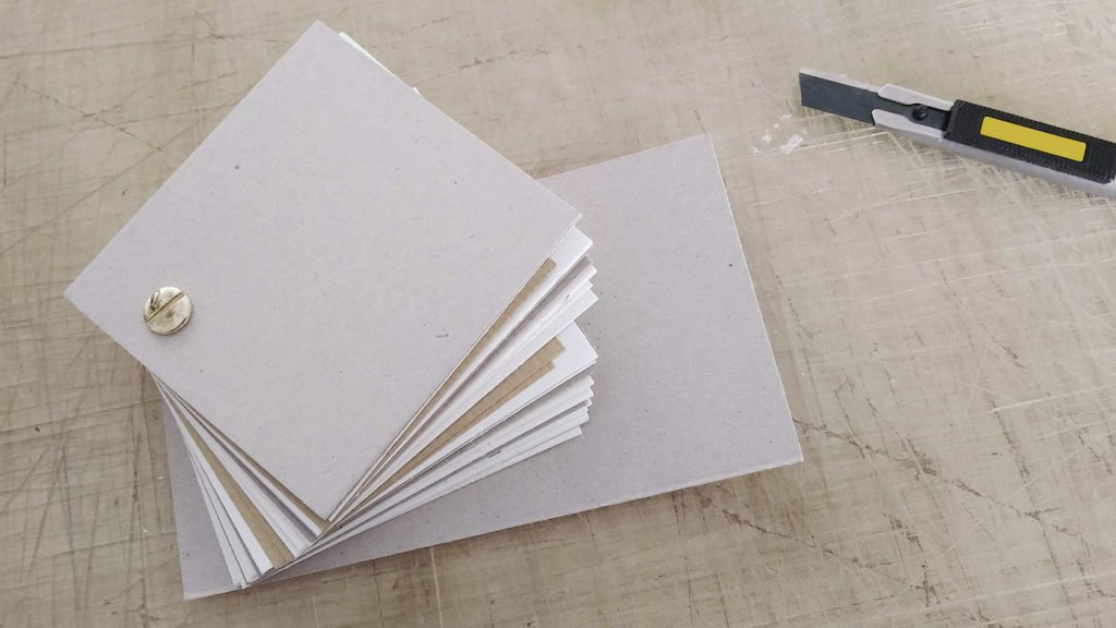Skizzenbuch aus dem Verschnitt an Papier im kleinen, quadratischen Format.