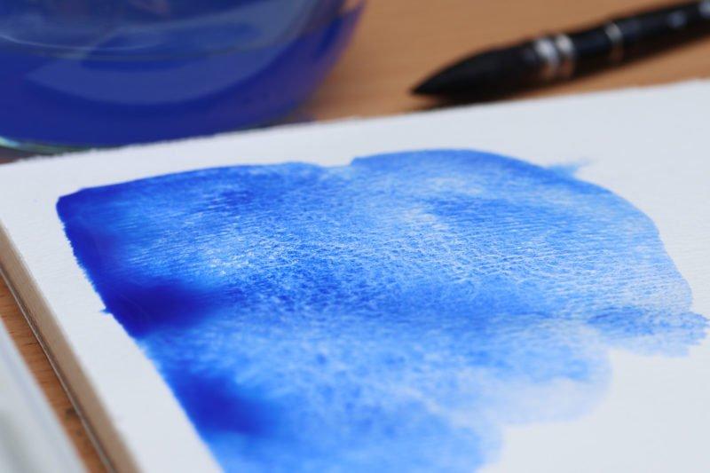 Aquarellfarbe bildet Strukturen auf dem Papier.