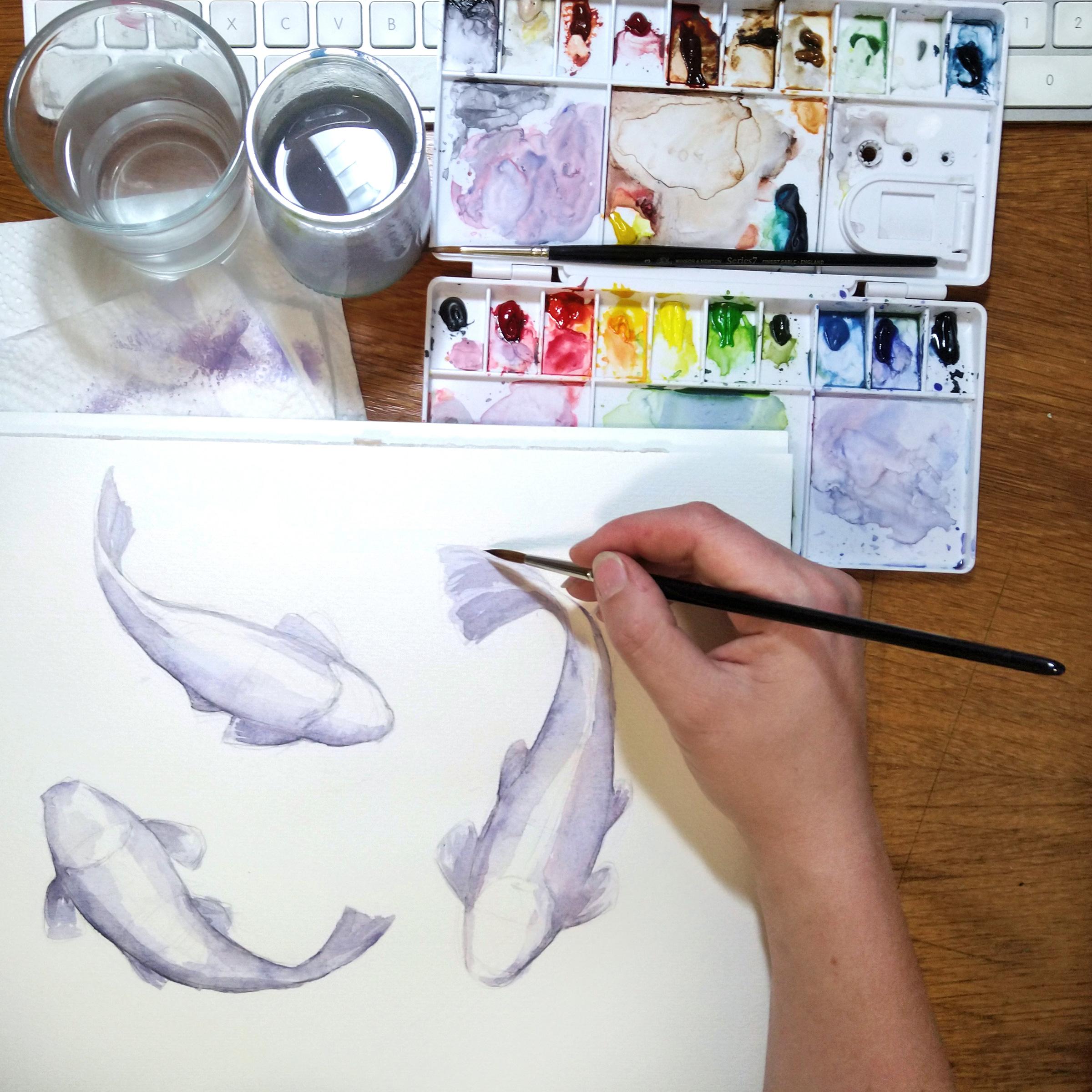 Nach der Skizze kommt die erste Farbe mit den Schatten der Kois auf das Papier