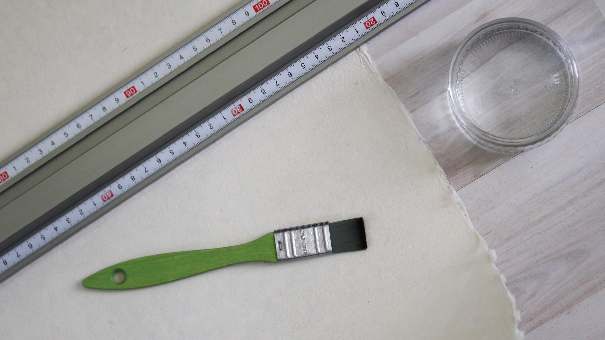 Zum Reißen des großen Bogens Büttenpapier benötigt man ein Metall-Lineal, klares Wasser und einen Pinsel.