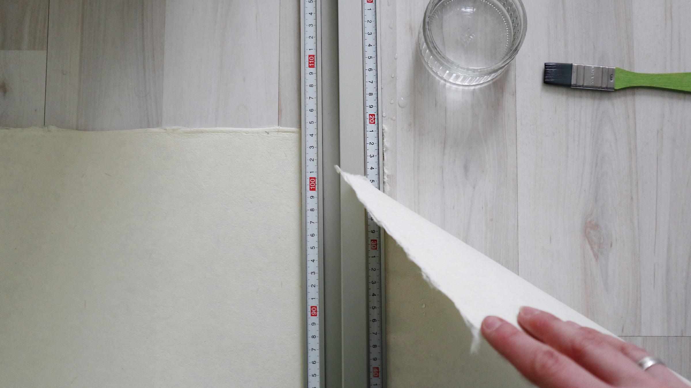 Metall-Lineal anlegen, gut festhalten und langsam und bedächtig am Papier ziehen so dass die Kante ausfasernd aufreisst.
