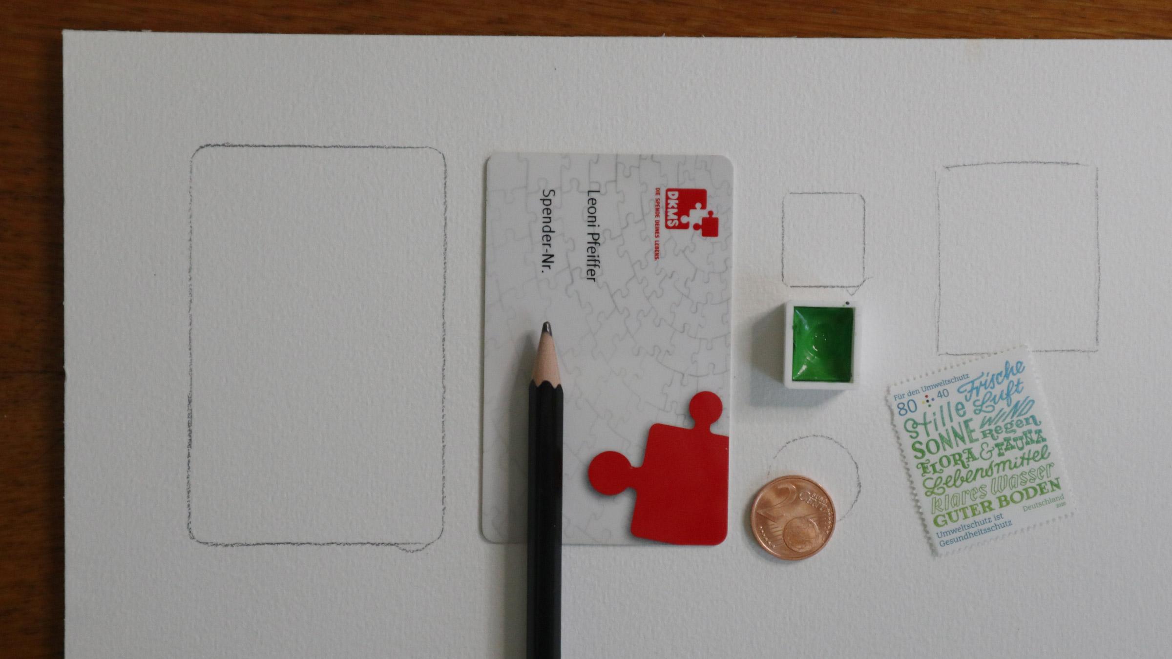 Verschiedene Dinge, die ein kleines Format gut vorgeben können: Eine Scheckkarte, der halbe Napf Aqauarellfarbe, eine Briefmarke oder ein Cent-Stück.