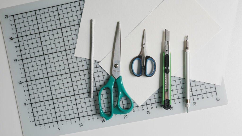 Material zum Schneiden von Papier Collagen: Silouttenschere, Cutter und Skalpell.