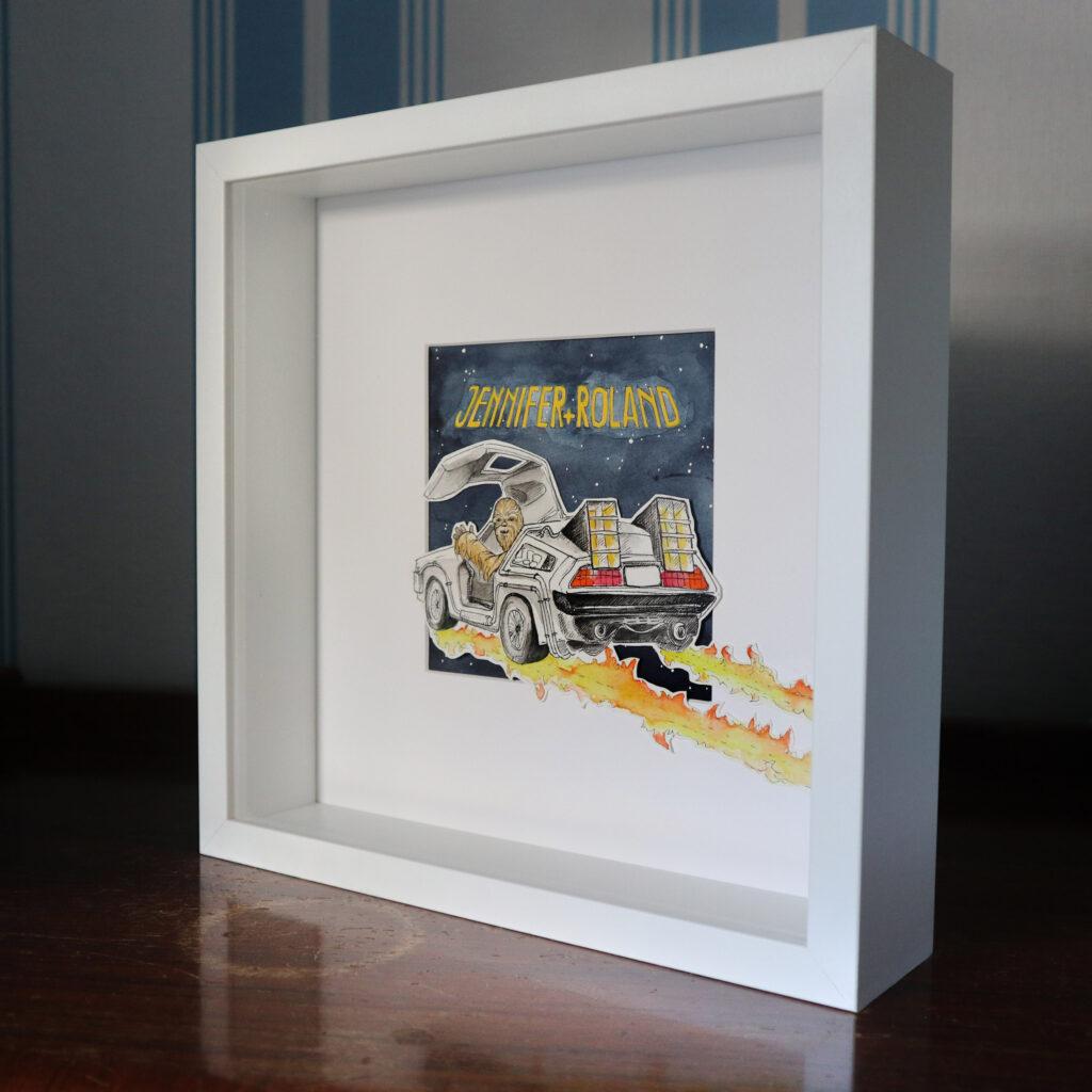 Der tiefe Bilderrahmen und die Collage mit dem Passepartout sorgen für Tiefe im Hochzeitsgeschenk. Fehlt nur noch das Geld angebunden an das Heck des DeLorean.