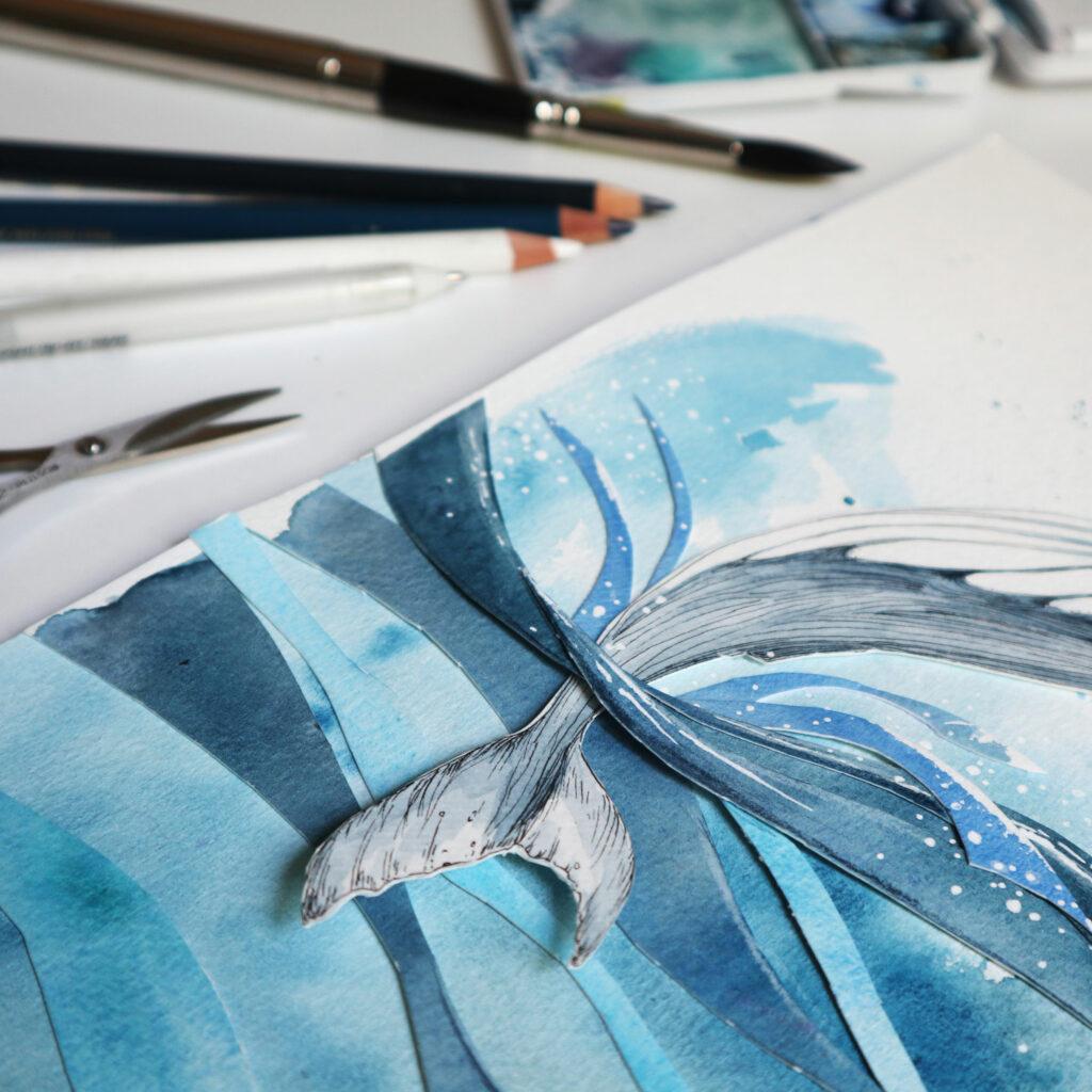 Detail der Walfluke über und unter den Wellen aus Papier.
