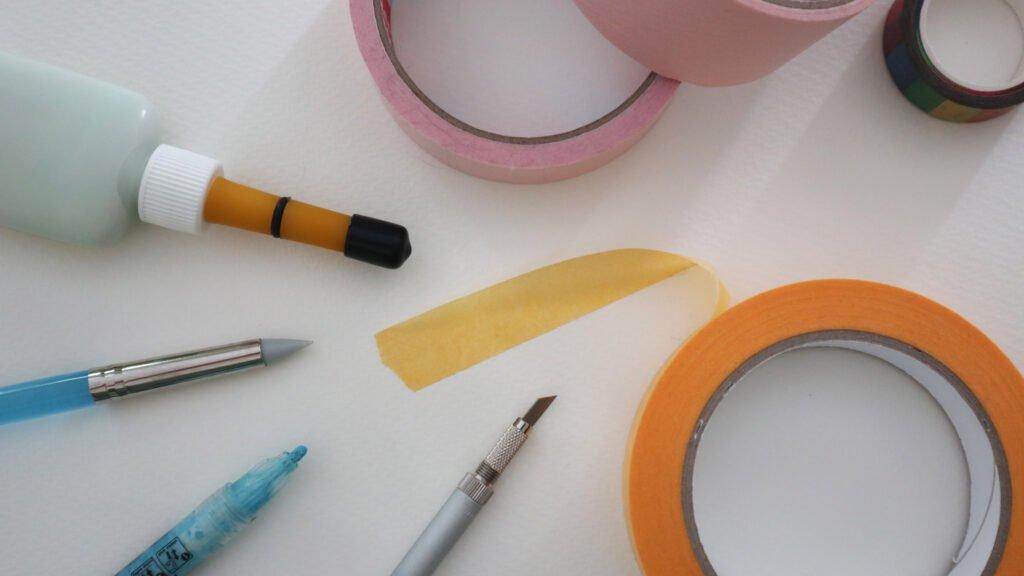 Materialien zum Maskieren: Maskiergummi, Silikonpinsel, Maskierstift, Klebeband und Skalpell.