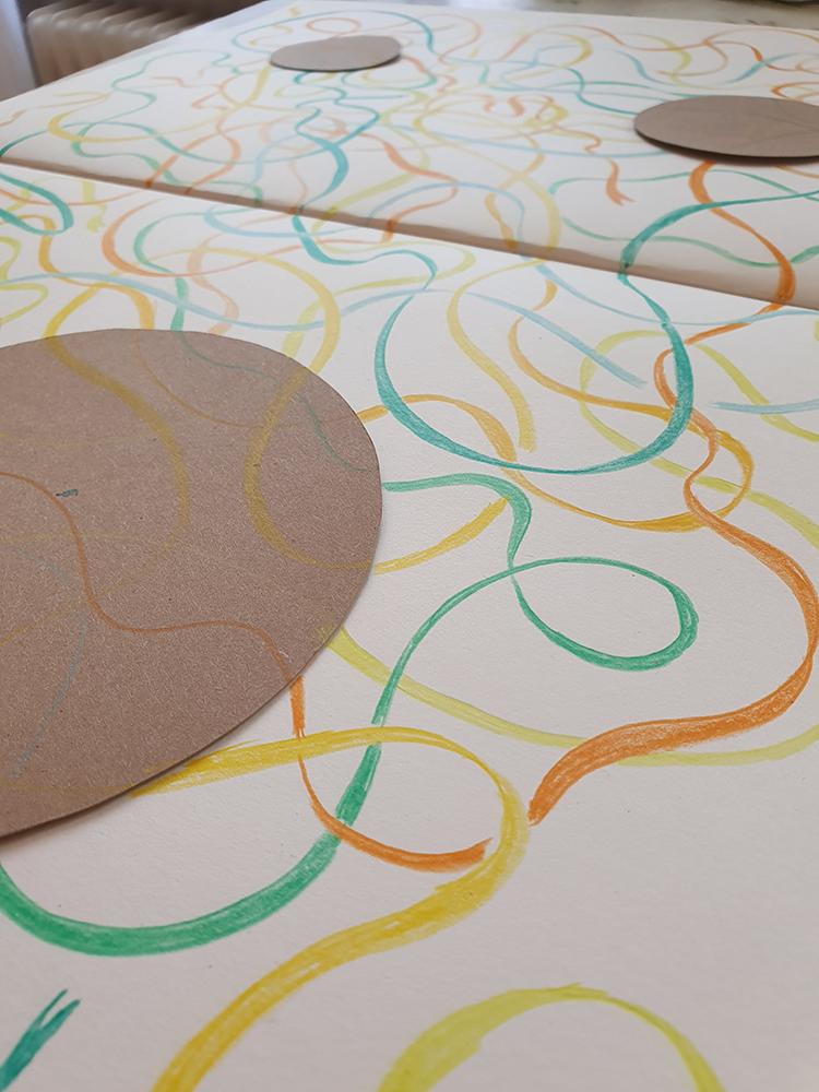Bänder aus Buntstift und Papierkreise, die das Papier abdecken.
