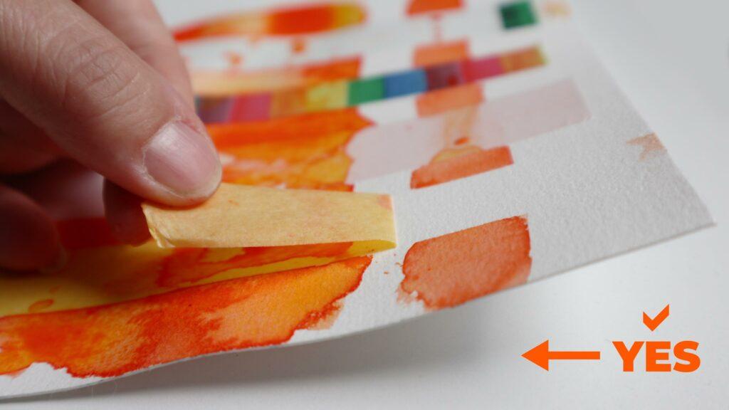 Parallel zum Papier: So sollte man Masking Tapes vom Aquarellpapier abziehen.
